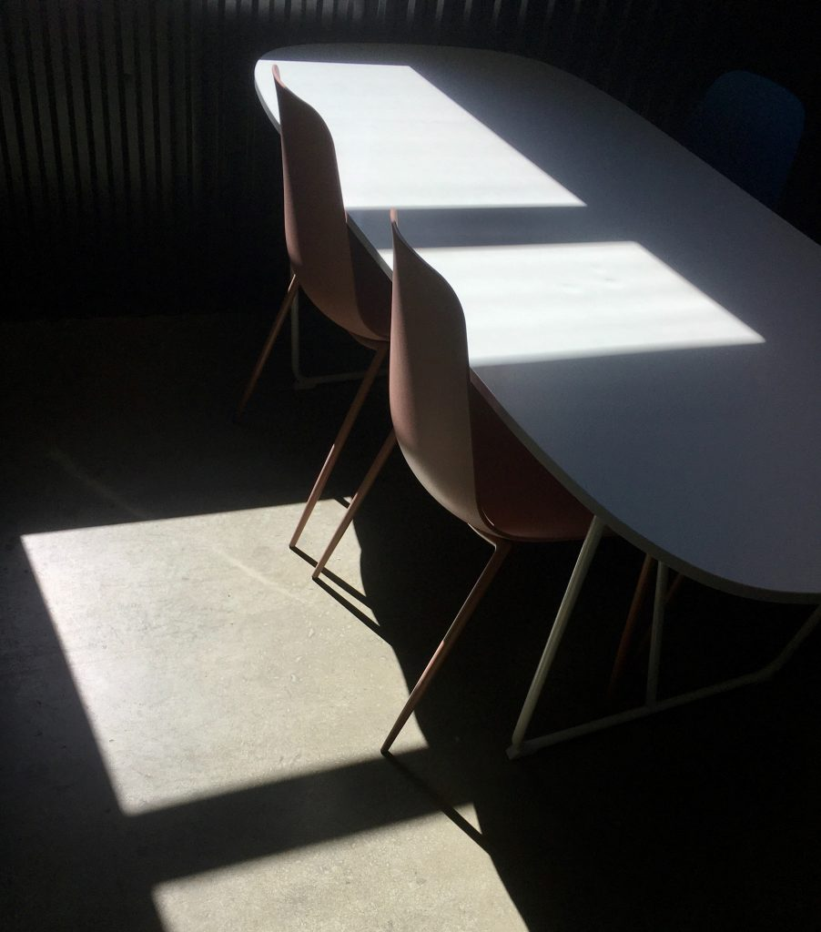 two empty chairs at a desk in the shadows