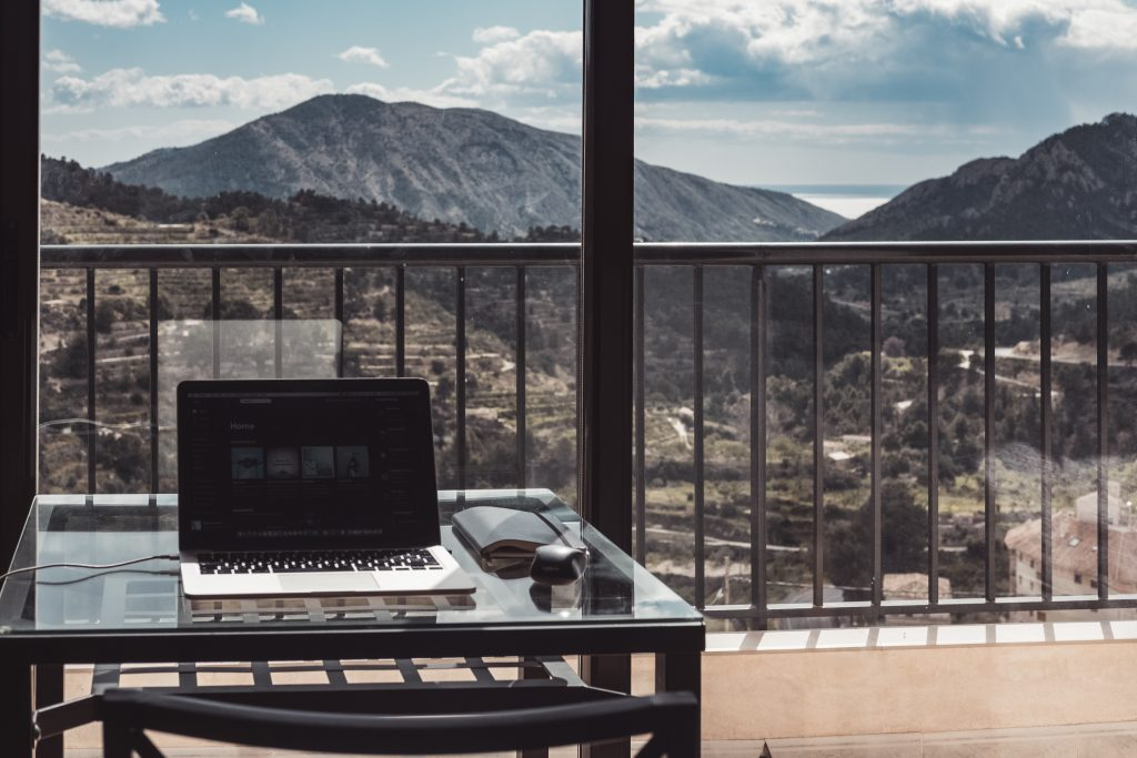 Laptop by a window overlooking mountains. Having the right tools for remote working.